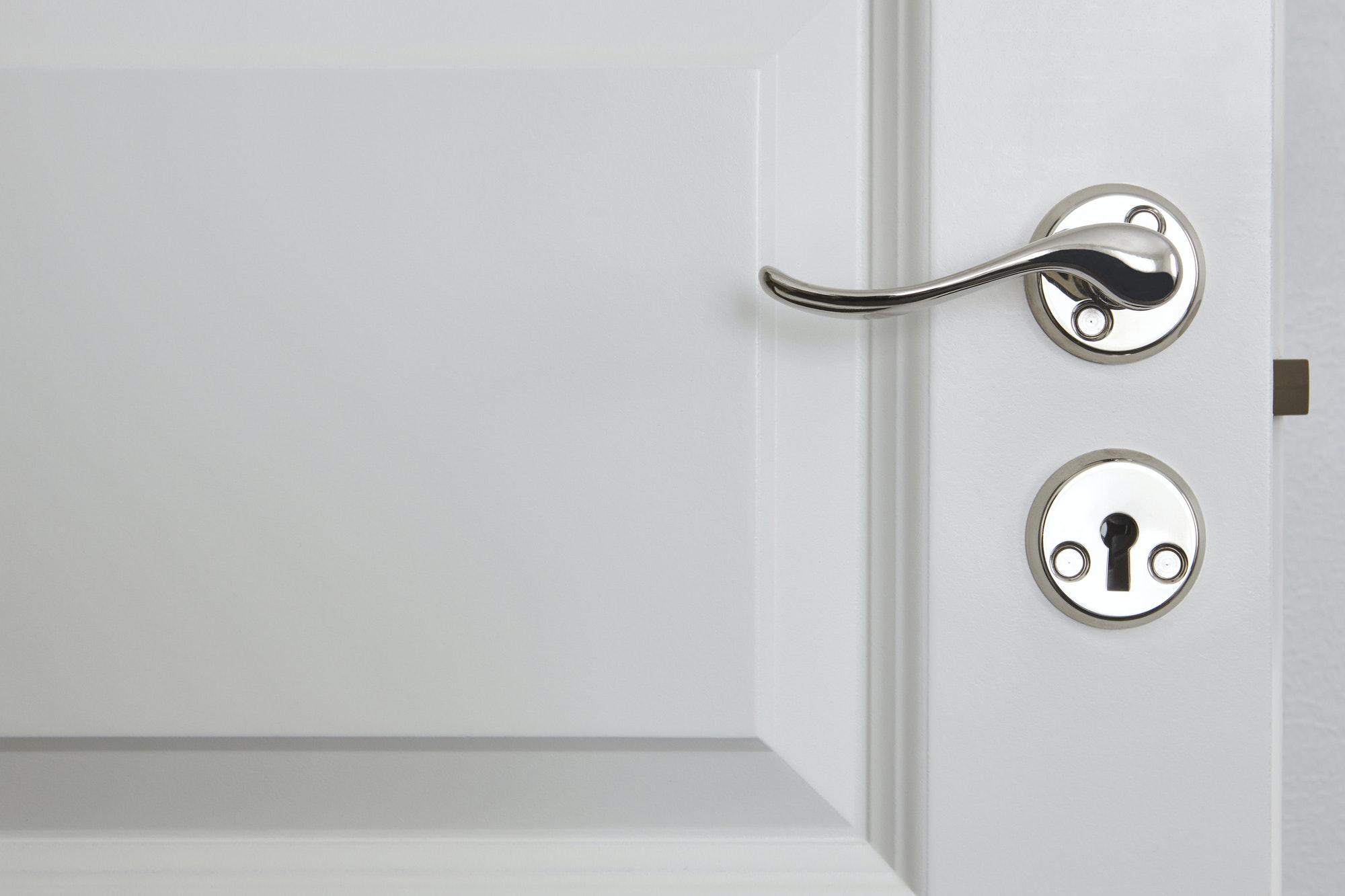 Metallic door knob on a classic white door. Home interior